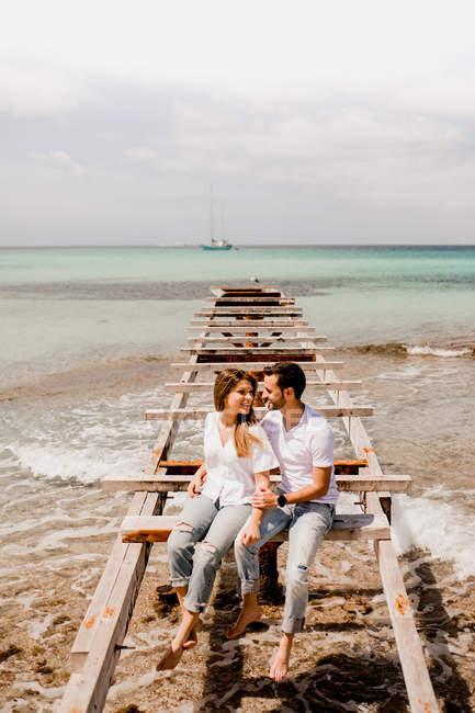 Glad lovers sitting on destroyed pier on seashore — Stock Photo