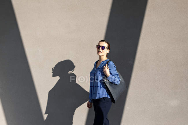 Manager in sunglasses and elegant outfit smiling and looking at camera while standing against gray building wall on city street — Stock Photo