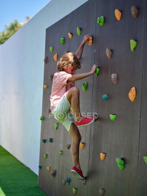 Boy climbing wall in yard — Stock Photo