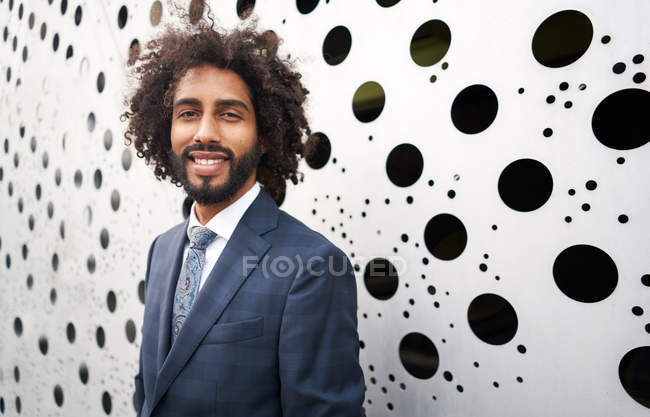 Cheerful african american entrepreneur standing next to holey wall — Stock Photo