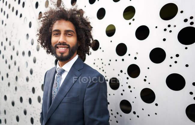 Allegro imprenditore afroamericano in piedi accanto alla parete buca — Foto stock