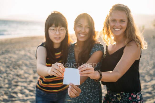 Drei attraktive Frauen umarmen sich mit einer Karte vor der Kamera und der Sonne im Rücken — Stockfoto