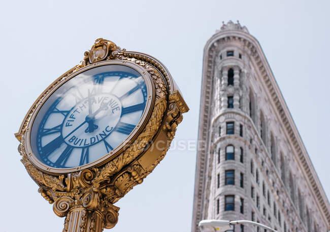 Desde abajo de reloj exquisito con la inscripción del edificio de la Quinta Avenida en él cerca del edificio Flatiron en el centro de Nueva York - foto de stock