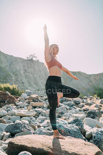 Миролюбивая женщина практикует йогу стоя на камне — стоковое фото