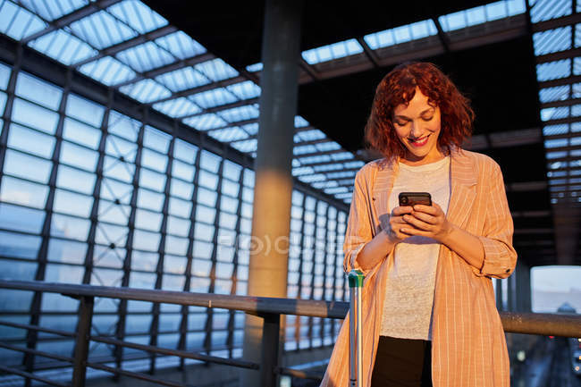 Smiling young woman browsing phone at station — Stock Photo