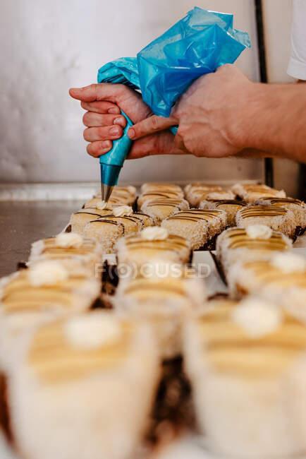 Человек на полях сжимает свежий крем из кондитерской поверх вкусной кондитерской во время работы в пекарне — стоковое фото
