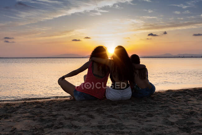 Back view of bronzed female friends hugging and relaxing on beach at sunset in summer in back lit — Stock Photo
