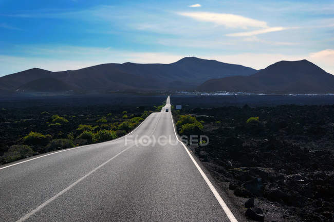 Empty curving road walking to mountain valley along dark field with greenery in Lanzarote Canary islands Spain — Stock Photo