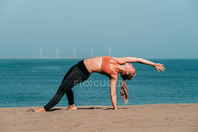Концентрированная женщина растягивается и занимается йогой на солнечном пляже — стоковое фото