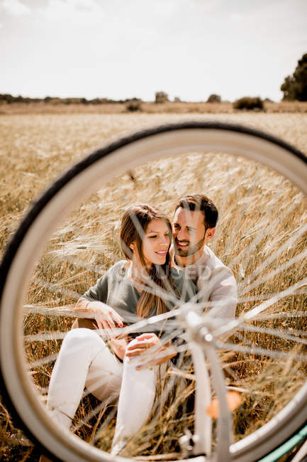 View through bicycle wheel of tender man and woman embracing on wheat field — Stock Photo