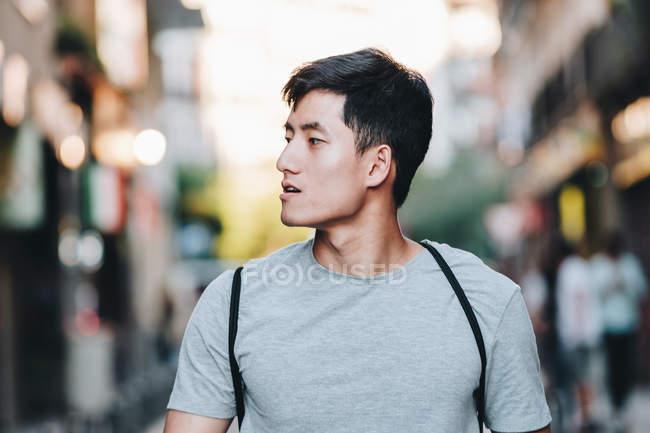 Conteúdo Homem asiático em t-shirt passeando ao longo urbano verão rua — Fotografia de Stock
