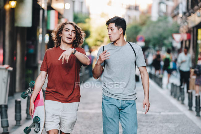 Carefree interested multiethnic men in casual clothes with longboard gesturing and talking while strolling along city street — Stock Photo