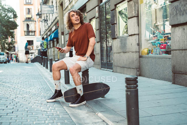 Cheerful casual man laughing and speaking on smartphone while sitting on baluster on city street — стокове фото