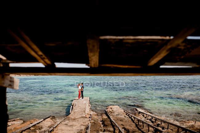 Ніжна пара на відстані обіймає узбережжя бірюзовою морською водою влітку. — стокове фото