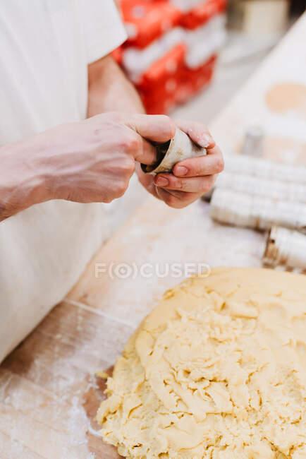 От анонимного кондитера, кладущего свежее мягкое тесто в маленькую чашку за столом в пекарне — стоковое фото