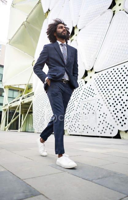 Dipendente afroamericano di successo in abito alla moda che cammina lungo la strada con le mani in tasca e distogliendo lo sguardo — Foto stock