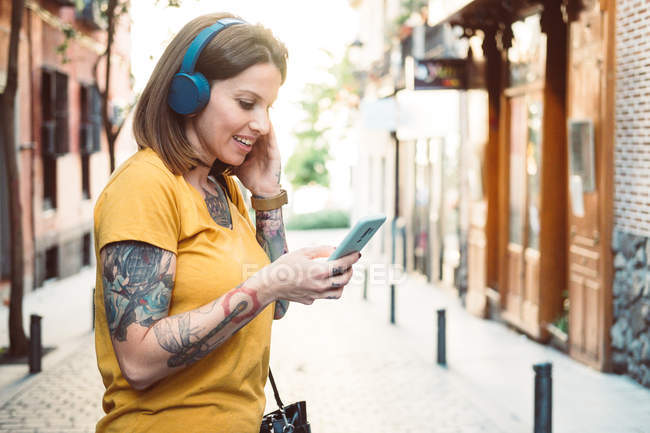 Attentive tattooed woman in headphones using smartphone while standing on sunny city street — Stock Photo