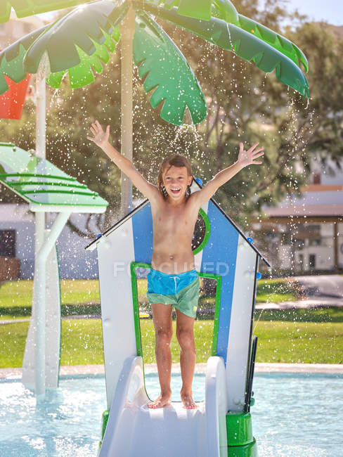 Cheerful boy standing on slide in water park — Stock Photo