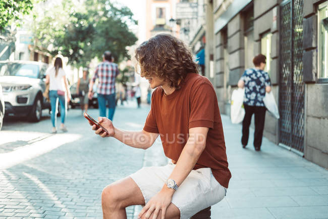 Cheerful casual man laughing and speaking on smartphone while sitting on baluster on city street — Stock Photo