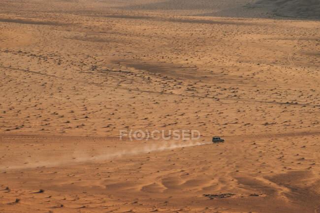 Offroader riding on sandy ground of Wadi Rum desert on sunny day in Jordan — Stock Photo
