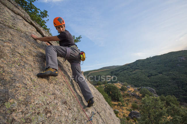 From below man climbing a rock in nature with climbing equipment — Stock Photo