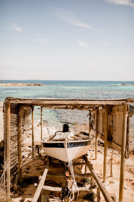 Barca ormeggiata sotto baldacchino in legno sulla spiaggia sabbiosa in estate luce del sole — Foto stock