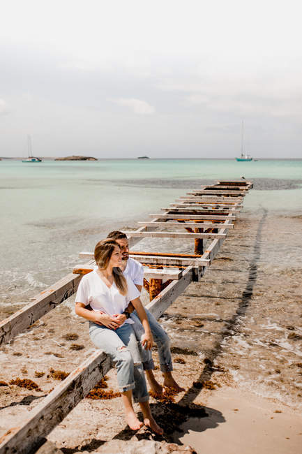 Romantic man and woman relaxing on aged old pier on beach of tropical seashore looking away — Stock Photo