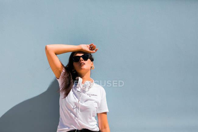 Bela mulher em roupa casual e fones de ouvido no pescoço de pé com as mãos para cima ao lado da parede azul de construção na rua da cidade — Fotografia de Stock
