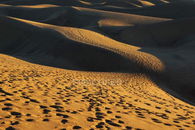 Следы на восковых песчаных склонах с контрастными тенями в солнечный день — стоковое фото