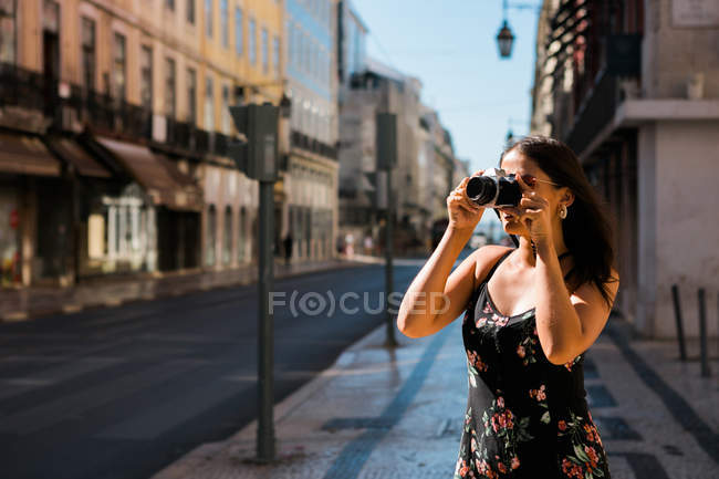 Confident woman in summer dress taking picture with camera while standing on scenic sunny city street in Lisbon, Portugal — Stock Photo