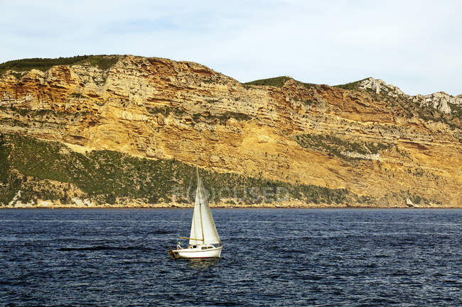 Белый парусник в море и красивые скалы — стоковое фото