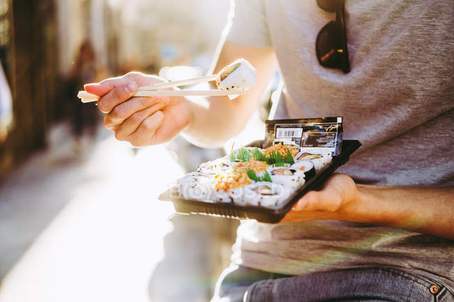 Cropped image of man eating takeaway food while standing by food truck on sunny street — Stock Photo