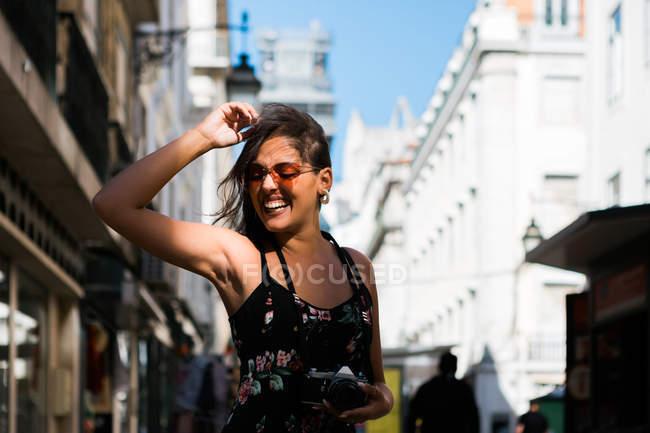 Игривая женщина в длинном платье с фотокамерой во время прогулки по летней улице города — стоковое фото
