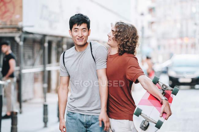 Hombres multiétnicos interesados despreocupados en ropa casual con gestos de longboard y hablar mientras pasean por la calle de la ciudad - foto de stock