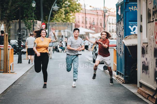 Sonriendo multiétnica gente competitiva en ropa casual corriendo y corriendo por la calle urbana - foto de stock