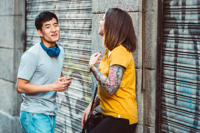 Positive multiethnic friends having conversation and gesturing while standing beside urban building — Stock Photo