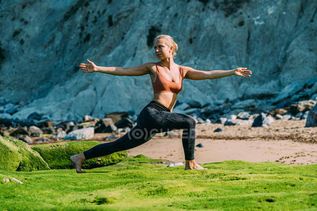 Woman practicing yoga on grassy meadow — Stock Photo