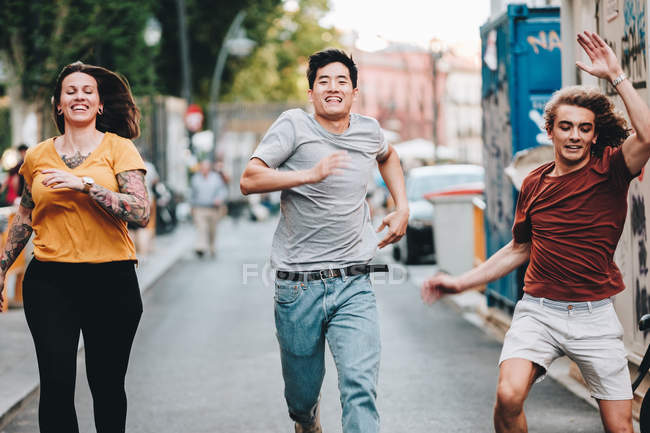 Lächelnde multiethnische Wettkämpfer in legerer Kleidung eilen und laufen die Stadtstraße entlang — Stockfoto