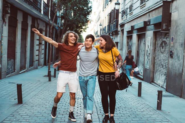 Счастливые беззаботные люди в повседневной одежде обнимаются и прогуливаются вместе по городской улице — стоковое фото