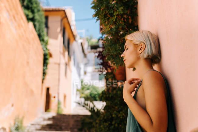 Вид сбоку на красивую молодую женщину с короткими светлыми волосами закрывая глаза и опираясь на стену на улице — стоковое фото
