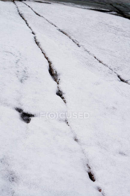 Close-up of processed rock surface with cracks and scratches covered with snow — Stock Photo