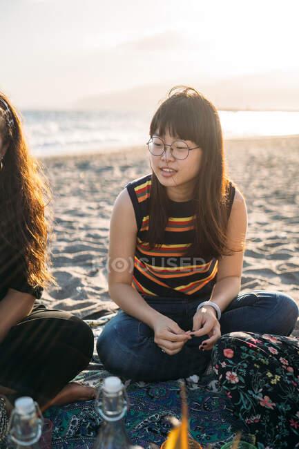 Porträt eines schönen asiatischen Mädchens an einem Tag am Strand mit ihren Freunden, die Sonne hinter sich — Stockfoto
