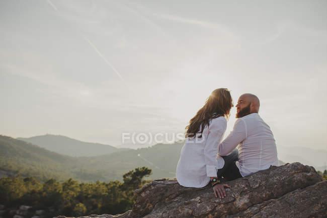 Счастливая пара, сидящая у горной скалы — стоковое фото