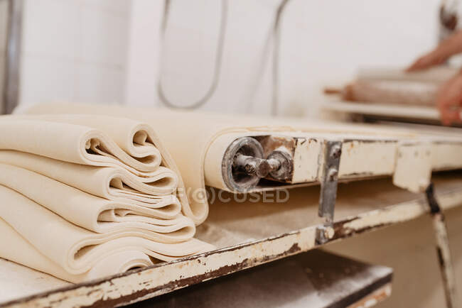 Shabby machine rolling fresh soft dough for pastry preparation in kitchen of professional bakery — Stock Photo