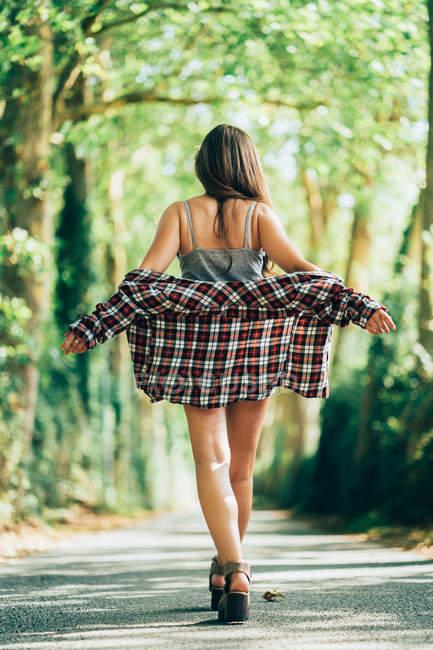 Vista trasera de la mujer con estilo en camisa de camisa con control de hombros y caminar a lo largo de un valle verde claro. - foto de stock