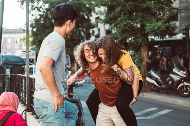 Грайливі багатонаціональні люди сміються і їздять верхи, стоячи на сонячній вулиці. — стокове фото