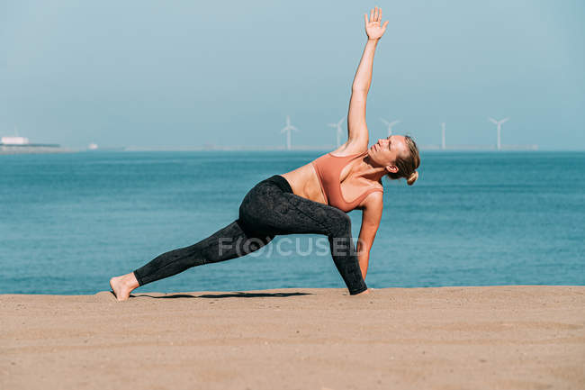 Concentrated woman stretching and doing yoga on sunny beach — Stock Photo