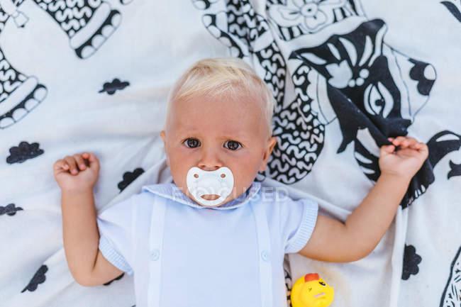 Верхний вид на блондинку с пустышкой на одеяле — стоковое фото