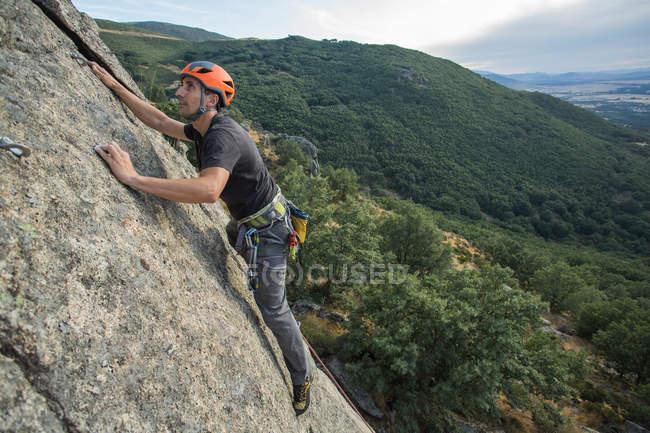Сверху человек взбирается на скалу в природе с альпинистским снаряжением — стоковое фото