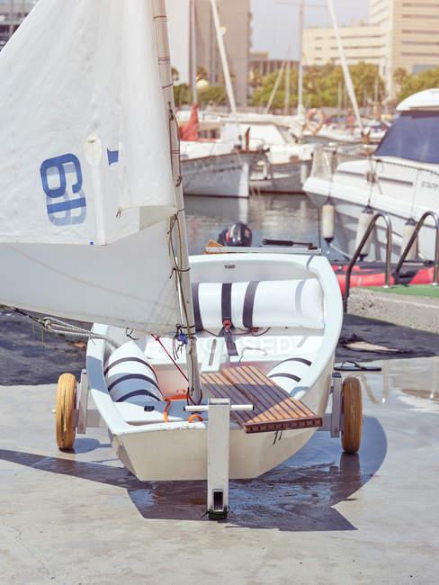 Barco compacto vacío de ruedas pequeñas con vela blanca listo para flotar - foto de stock